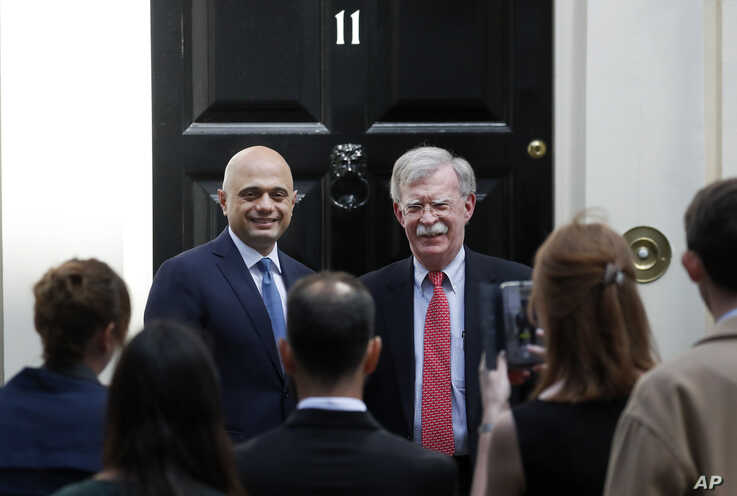 John Bolton, President Donald Trump's national security adviser, right, is welcomed at Downing Street by Britain's Chancellor of the Exchequer Sajid Javid in London, Britain, Aug. 13, 2019.