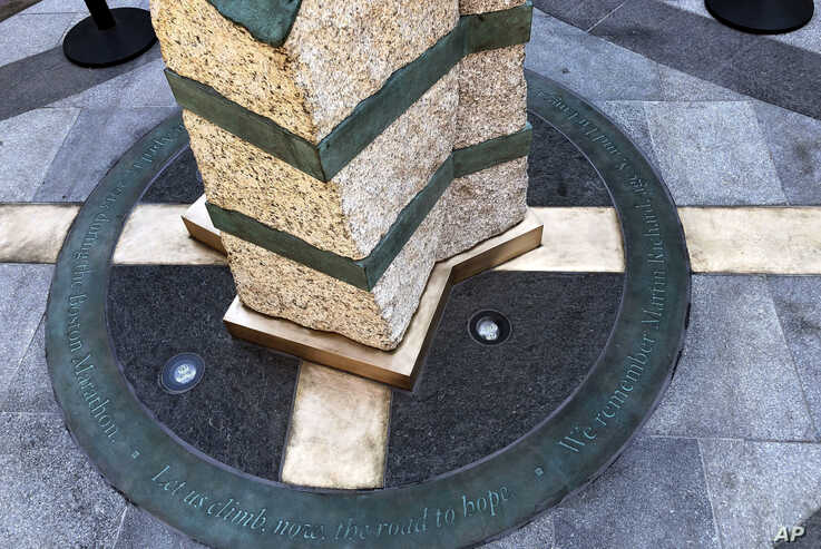 Inscriptions ring the base of two of the stone pillars completed Aug. 19, 2019, in Boston to memorialize the Boston Marathon bombing victims at the sites where they were killed.