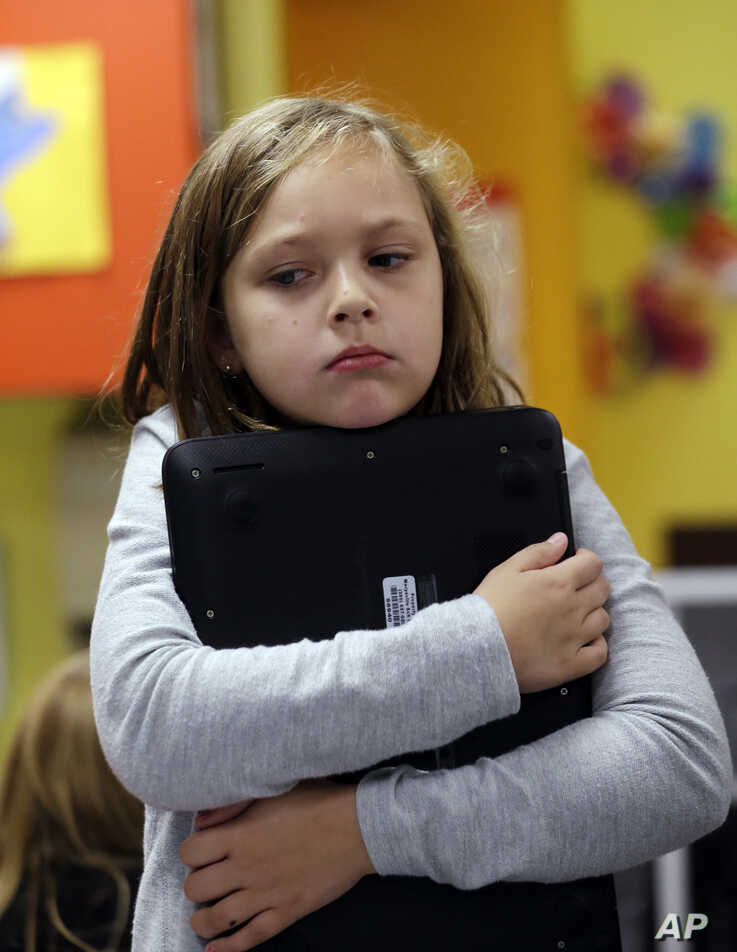 FILE - Second-grader Annabelle Davis hugs a laptop commuter to her chest during a weekly computer science lesson in Marysville,