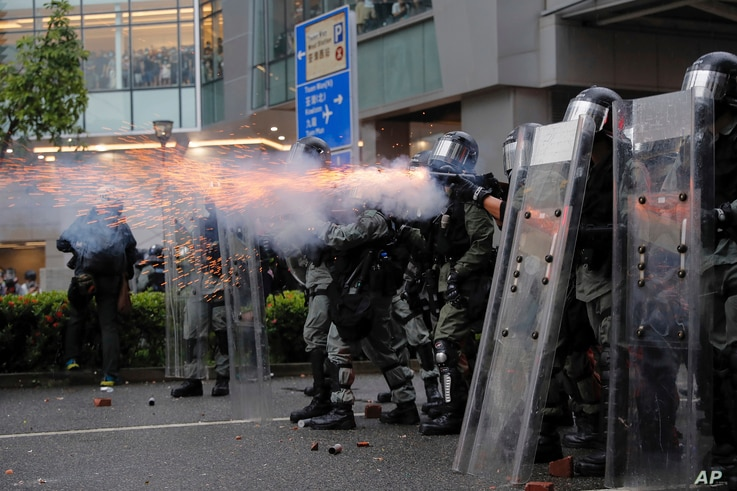 Riot police fire tear gas at protesters in Hong Kong, Aug. 25, 2019.