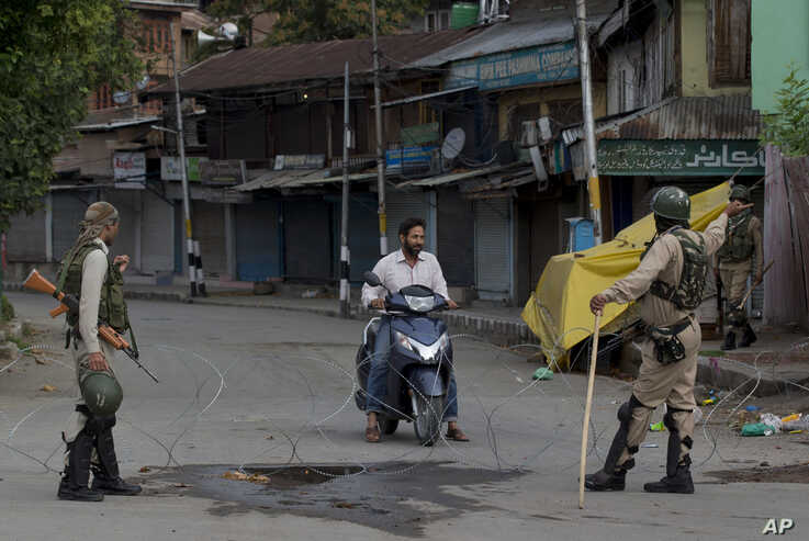 Indian paramilitary soldiers turn back a Kashmiri motorist near a temporary check point during lockdown in Srinagar, Aug. 18, 2019.