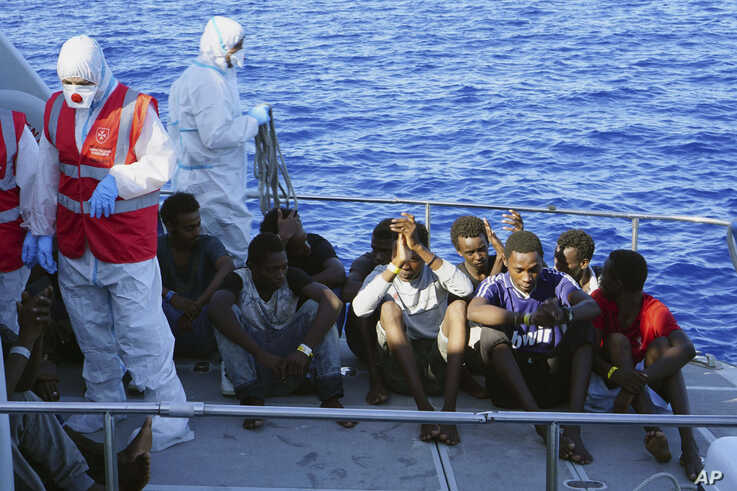 FILE - Migrants are evacuated by Italian Coast guards from the Open Arms Spanish humanitarian boat at the coasts of the Sicilian island of Lampedusa, southern Italy, Aug. 17, 2019.