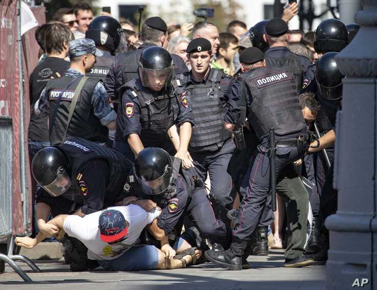 Police officers detain protesters during an unsanctioned rally in the center of Moscow, Russia, July 27, 2019.