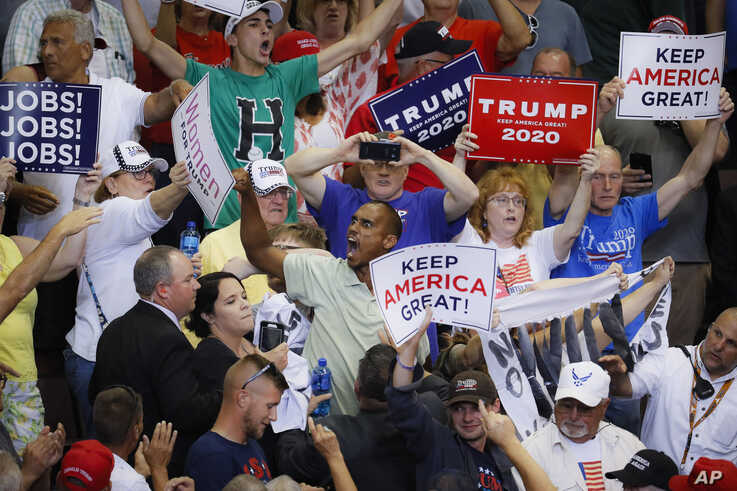 Supporters wave signs as President Donald Trump speaks at a campaign rally at U.S. Bank Arena, in Cincinnati, Ohio, Aug. 1, 2019.