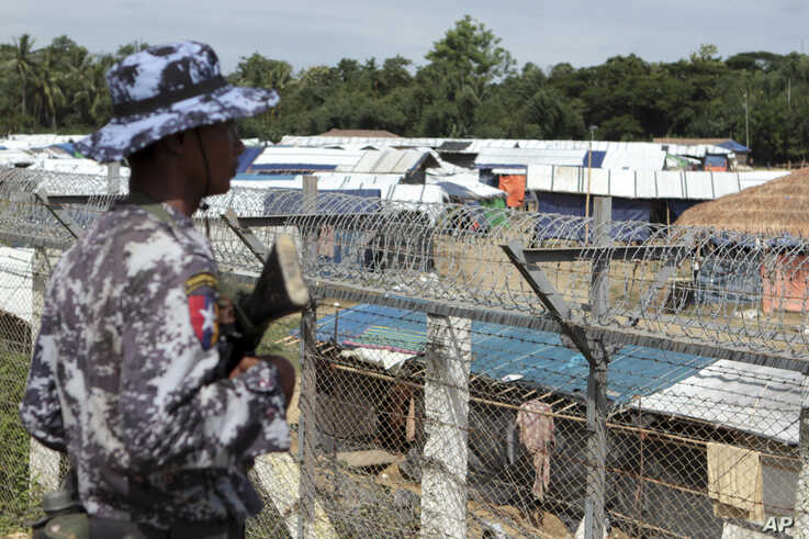 A Myanmar guard patrols outside a fenced-in camp during a government-organized media tour to a no-man's land between Myanmar and Bangladesh, near Taungpyolatyar village, Maung Daw, northern Rakhine State, Myanmar, June 29, 2018.