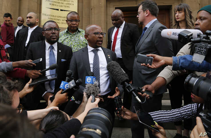 Nelson Mandela Foundation CEO Sello Hatang (C) speaks to the press on the steps of the Johannesburg High Court, Aug. 21, 2019.