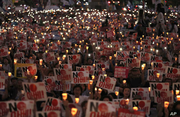 Protesters hold candles and signs during a rally denouncing Japanese Prime Minister Shinzo Abe and also demanding the South Korean government cancel its GSOMIA agreement with Japan, in downtown Seoul, South Korea, Aug. 15, 2019.