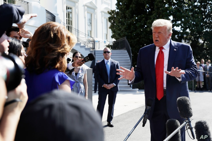 President Donald Trump talks to reporters on the South Lawn of the White House, Aug. 9, 2019, in Washington.