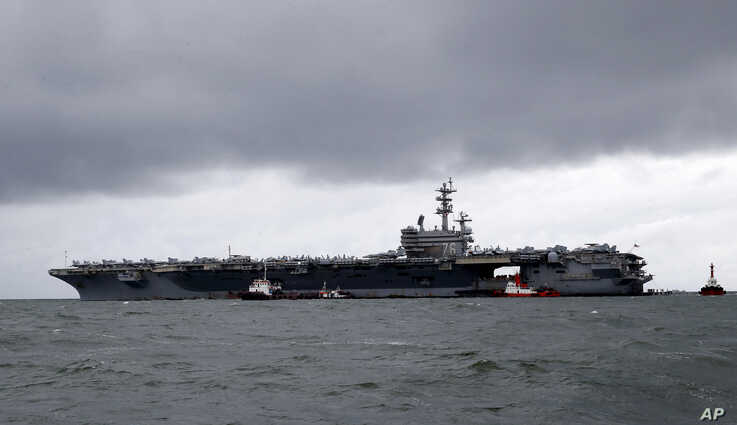 The U.S. aircraft carrier USS Ronald Reagan is seen anchored off Manila Bay, Philippines, Aug. 7, 2019, for a port call after sailing through the disputed South China Sea amid new territorial flare-ups involving China and rival claimant states.