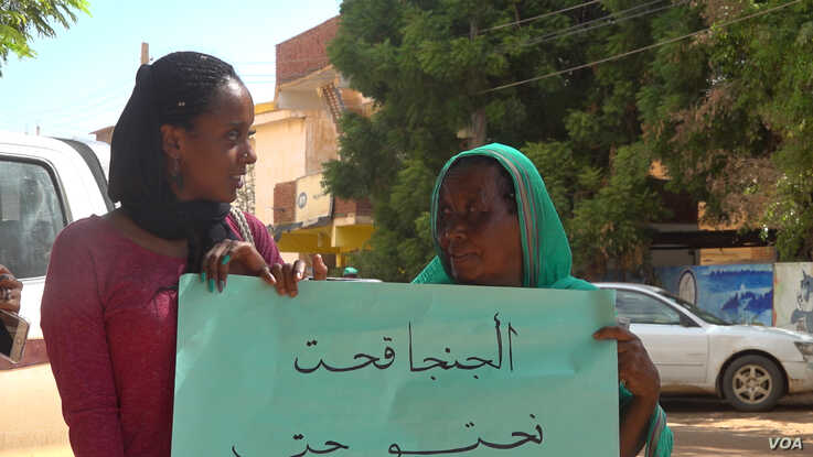 Nahid Bustami shares her protests sign with another woman (E. Sarai/VOA)