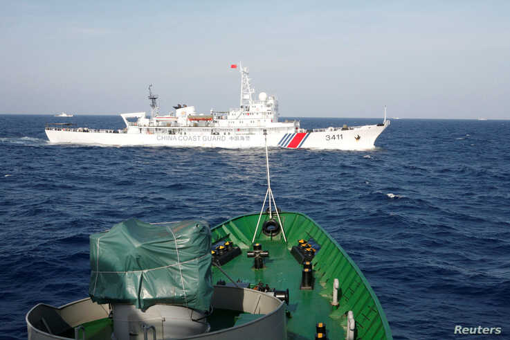 A ship (top) of the Chinese Coast Guard is seen near a vessel of the Vietnam Marine Guard, in the South China Sea, about 210 km (130 miles) off the shore of Vietnam, May 14, 2014.