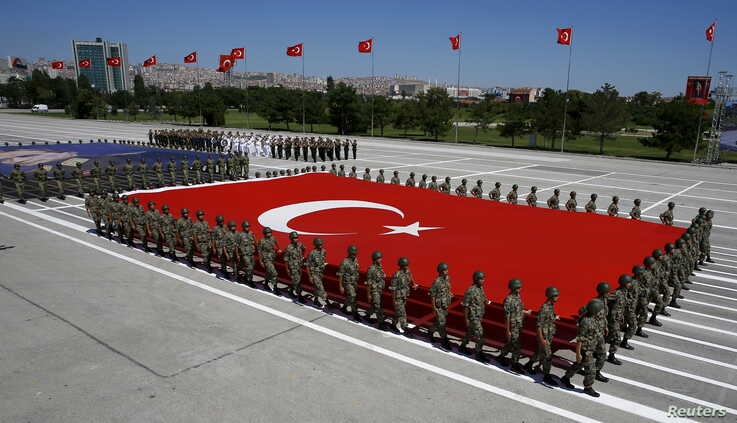 Turkish soldiers carry a huge national flag and a portrait of Mustafa Kemal Ataturk, founder of modern Turkey, during a military parade in Ankara, Turkey, Aug. 30, 2015.