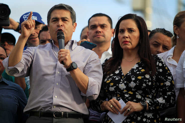 Honduran President Juan Orlando Hernandez, accompanied by his wife Ana Garcia, addresses supporters during a rally outside the Presidential House, in Tegucigalpa, Aug. 6, 2019.