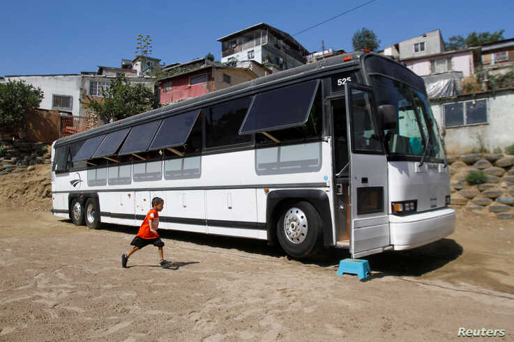 A migrant child runs towards a bus converted in a classroom as part of Schools On Wheels program by California's 'Yes We Can' organization, in Tijuana, Mexico, Aug. 2, 2019.