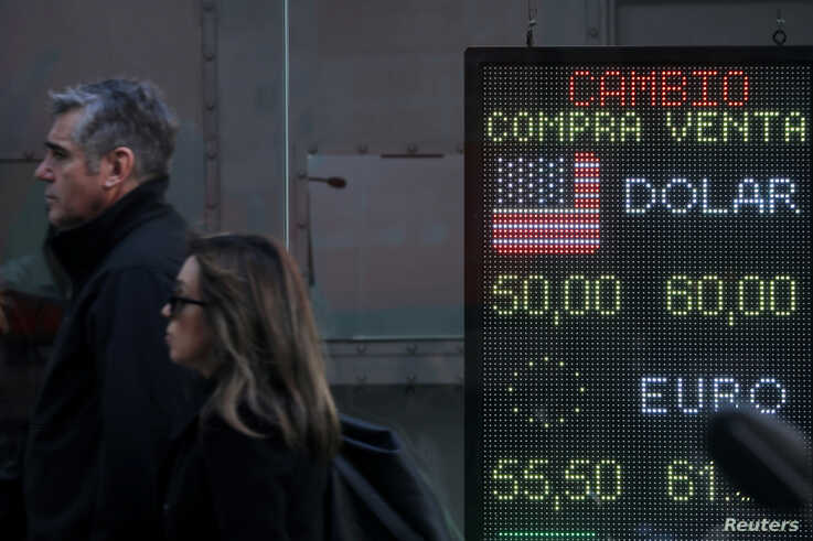 Pedestrians walk past an electronic board showing currency exchange rates in Buenos Aires' financial district, Argentina, Aug. 12, 2019.