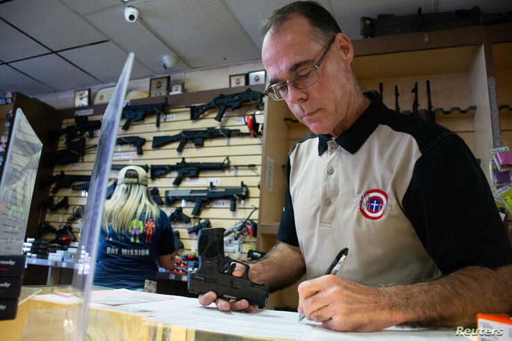 Gun Central general manager Michael McIntyre examines and registers a handgun for sale following the attack that killed 22 people in a Walmart on August 3, in El Paso, Texas, Aug. 12, 2019.