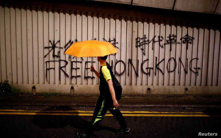 A man walks past a graffiti during a march to demand democracy and political reforms in Hong Kong, China, Aug. 18, 2019.