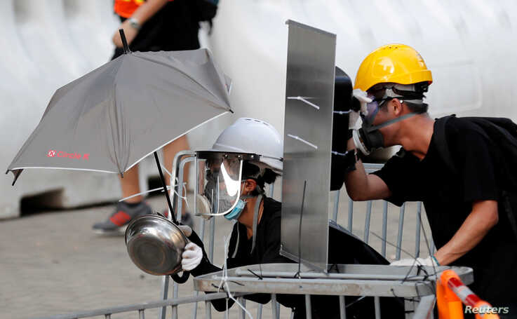 Protesters use makeshift protective gear to avoid tear gas during the city-wide strike to call for democratic reforms outside Central Government Complex in Hong Kong.
