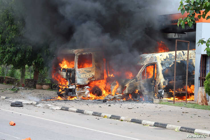 FILE - An ambulance and a fire engine set on fire by a Shi'ite group are seen at the Federal Secretariat in Abuja, July 22, 2019.