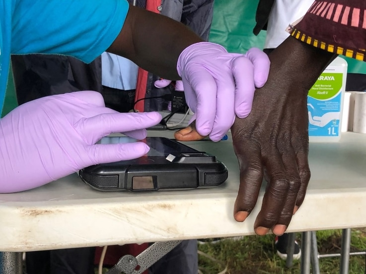 A woman's fingerprints are scanned before receiving a cash voucher at the Lobule refugee settlement in Uganda. August 14, 2019 (T. Krug/VOA)