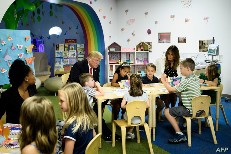 FILE - U.S. President Donald Trump and First Lady Melania Trump visit children at Nationwide Children's Hospital in Columbus, Ohio, Aug. 24, 2018. A Chinese American couple has been charged with stealing scientific trade secrets from the hospital.