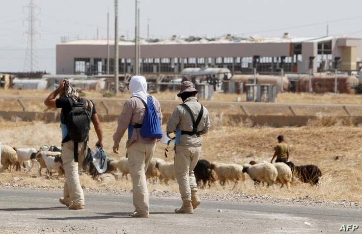Iraqi mine clearers working with Halo Trust, a non-profit organization specialized in mine removal, prepare to scan an agricultural area near Iraq's Baiji, Aug. 25, 2019.