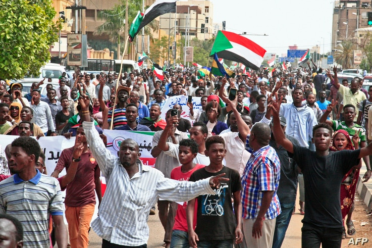 People wave the old and current flags of Sudan as they chant slogans during a mass demonstration near the presidential palace in Sudan's capital, Khartoum, Sept. 12, 2019.