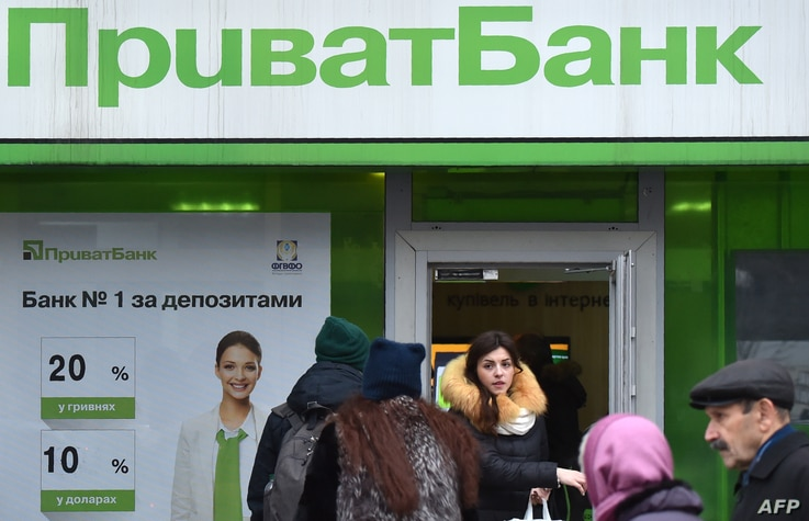 FILE - A client walks out as others arrive at the office of the PrivatBank in the center of Kyiv, Dec. 19, 2016.