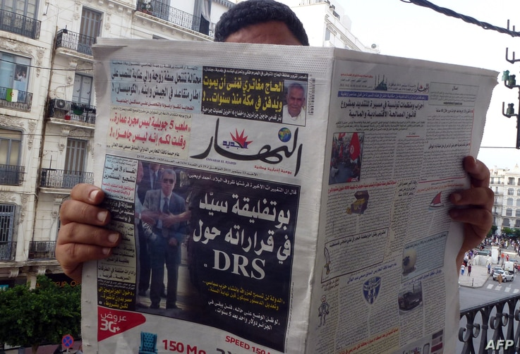 FILE - An Algerian man reads a local newspaper, En-Nahar, bearing a picture for the first time of former Algerian intelligence chief General Mohamed Mediene, better known as General Toufik, on the front cover in the capital, Algiers, Sept. 13, 2015.