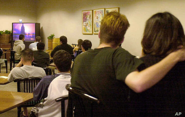 Students and others watch live television coverage of the 9/11 attacks on the UCLA campus in Los Angeles, Sept. 11, 2001.