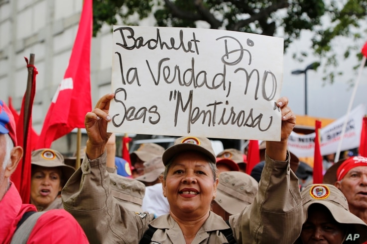 "FILE - A member of the Bolivarian militia holds up a sign that reads in Spanish: ""Bachelet tell the truth"" during a protest against Michelle Bachelet, the U.N. high commissioner for human rights, in Caracas, Venezuela, July 13, 2019."
