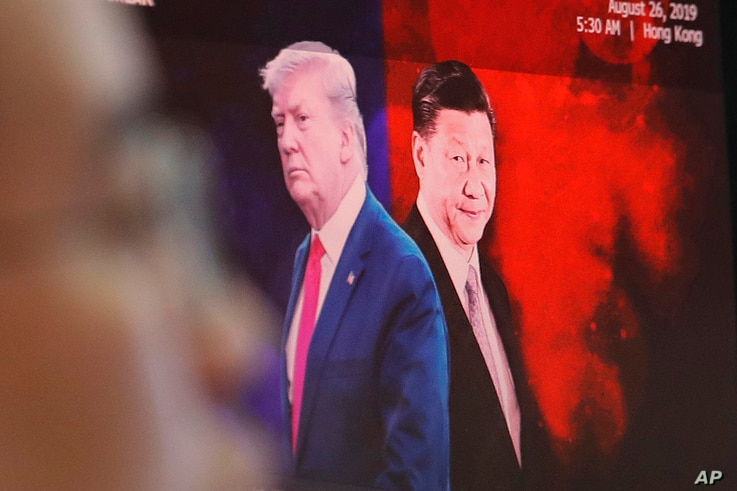 FILE - A computer screen shows images of Chinese President Xi Jinping, right, and U.S. President Donald Trump as a currency trader works at the KEB Hana Bank headquarters in Seoul, South Korea, Aug. 26, 2019.