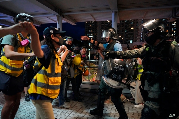People block policemen who arrive to arrest protesters at Tung Chung near airport in Hong Kong, Sunday, Sept.1, 2019.