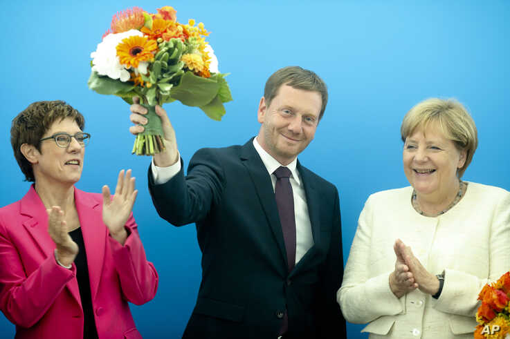 German Chancellor Angela Merkel, right, and Christian Democratic Union party's chairwoman Annegret Kramp-Karrenbauer, left, applause to Governor of Saxony Michael Kretschmer prior to a party's board meeting, Sept. 2, 2019.