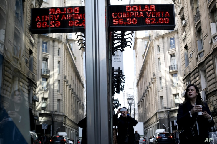 A woman walks under a sign showing exchange rates between the U.S. dollar and Argentine peso in Buenos Aires, Argentina, Sept. 2, 2019.