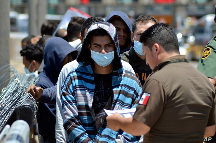 FILE - Mexican officials and U.S. Border Patrol officers return a group of migrants to the Mexico side of the border as Mexican immigration officials check the list, in Nuevo Laredo, Mexico, July 25, 2019.