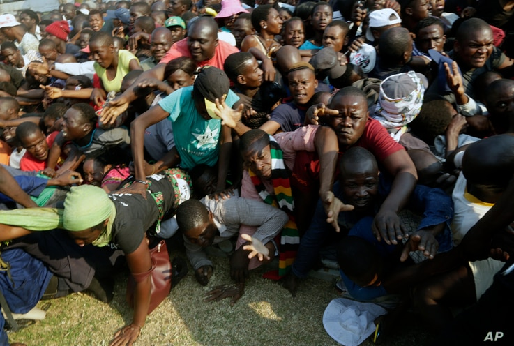 Mourners stampede after the arrival of the coffin carrying former President Robert Mugabe at the Rufaro Stadium in Harare, Sept. 12, 2019.