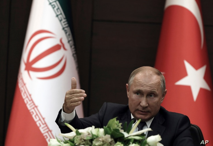 FILE - Russia's President Vladimir Putin speaks during a joint news conference with Turkish President Recep Tayyip Erdogan and Iran's President Hassan Rouhani, in Ankara, Turkey, Sept. 16, 2019.