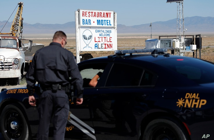 Law enforcement officials stand outside of the Little A'Le'Inn, Wednesday, Sept. 18, 2019, in Rachel, Nev.