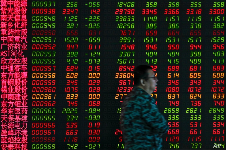 In this Sept. 19, 2019, photo, a man walks by an electronic board displaying stock prices at a brokerage house in Beijing.