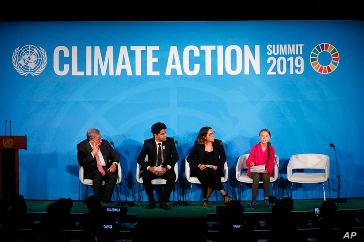 U.N. Secretary-General Antonio Guterres, far left, and young environmental activists look on as Greta Thunberg, of Sweden, in red, addresses the Climate Action Summit in the United Nations General Assembly, at U.N. headquarters, Sept. 23, 2019.