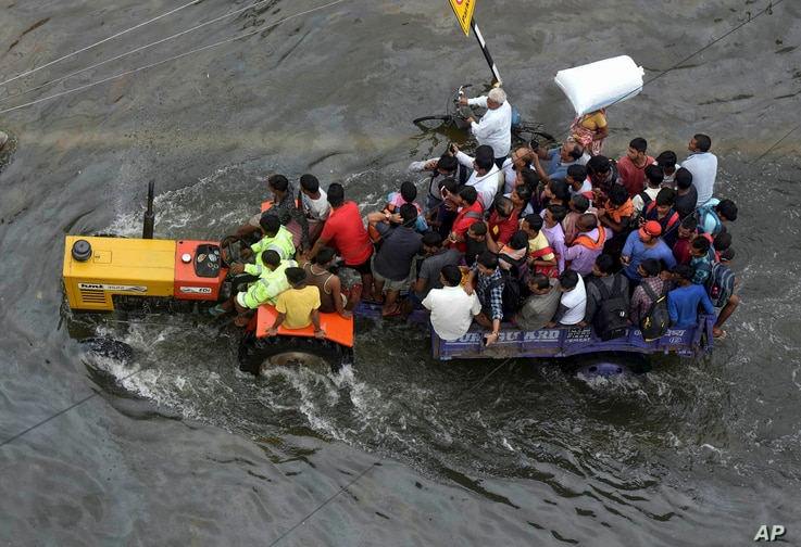 People are rescued in a tractor from a flooded area following heavy rainfall in Patna, India, ept.30, 2019.