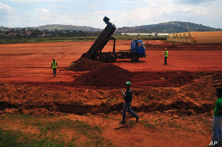 FILE - Dirt is cleared and dumped, destroying a wetland in Entebbe, Uganda, July 8, 2013.