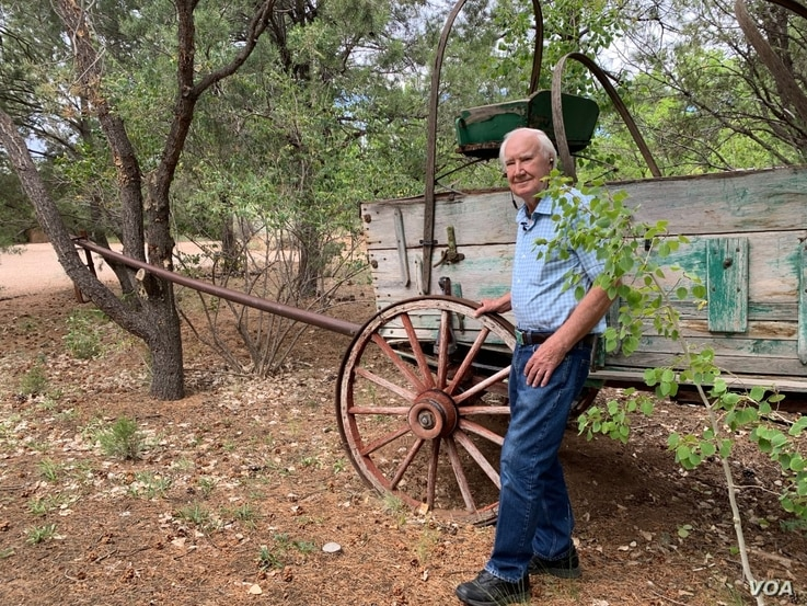 Forrest Fenn stands in front of an original 19th century cart he had placed on the old Santa Fe trail running through his property.
