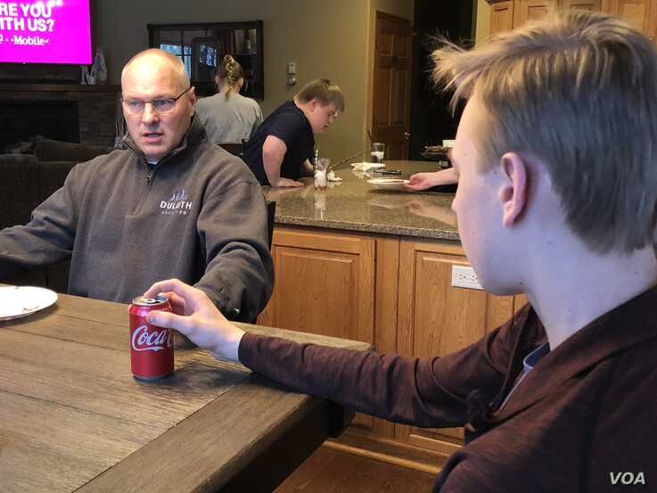 Rep. Stauber in a rare relaxing moment at home in Duluth, Minn., with his son Luke. (Photo: C. Presutti / VOA)