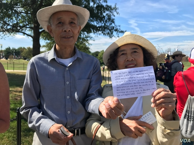 A Chinese couple sought tickets to the reopening of the Washington Monument in Washington, Sept. 19, 2019. They said their ancestors donated a stone on the 10th floor of the monument. (P. Widakuswara/VOA)