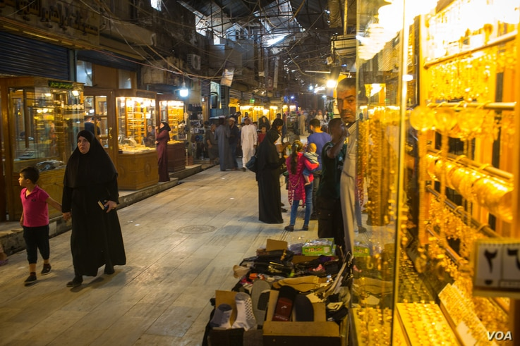 In a market in Manbij, Syria, locals say they have adapted to the rule of four different forces in the past eight years, and wil