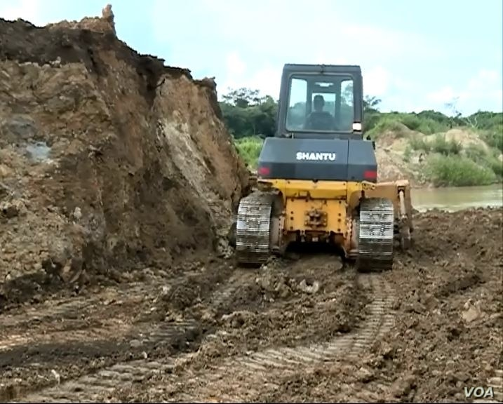 Mining companies in the Meiganga area use heavy equipment that lets them detect gold faster than locals who use manual tools.  Locals are paid about $2 per day to work at the Chinese mining sites. (M. Kindzeka/VOA)