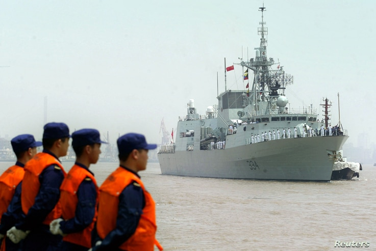 FILE - Chinese seamen stand as they welcome the arriving Canadian Navy Frigate, HMCS Regina in the port of Shanghai, Aug. 15, 2006.