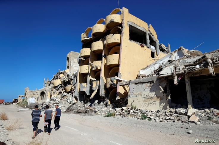 FILE - Youths walk past buildings that were destroyed during clashes between Libyan forces and Islamic State militants in Sirte, Libya, November 1, 2017.